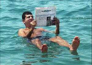 A man reading a newspaper while floating in the Dead Sea